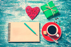 Notepad, cup of coffee, box with gift on a blue wooden table. Space for text Royalty Free Stock Photo