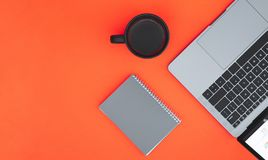 Notepad, a cup of coffee and a laptop are isolated on a red background and a place for the text royalty free stock image