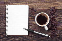 Notepad and cup of coffee Stock Images
