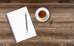 Notepad with cup of coffee on wooden table. Stock Photography