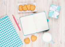 Notepad, cup of milk, heart shaped cookies and gift box Stock Photography