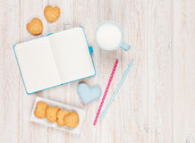 Notepad, cup of milk, heart shaped cookies and gift toy Stock Images