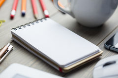 Notepad on the desk next to cup tablet and smartphone Stock Photo