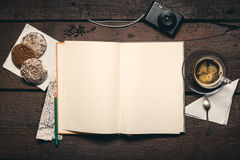 Notepad on the desktop. Blank page of notepad on the wooden table, honey-cake, compact camera, pencil and cup of espresso Royalty Free Stock Photo