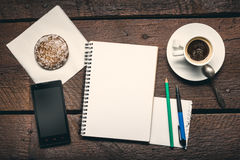 Notepad on the desktop. Blank page of notepad on the wooden table, honey-cake, smartphone, pen and pencil and cup of espresso Royalty Free Stock Photo