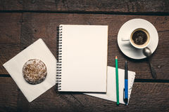 Notepad on the desktop. Blank page of notepad on the wooden table. Pen, pencil, cup od coffee and honey-cake Stock Images