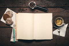Notepad on the desktop. Blank pages of notepad on the wooden table, Coffee beans in filter holder, cup of espresso and three honey-cakes Royalty Free Stock Image