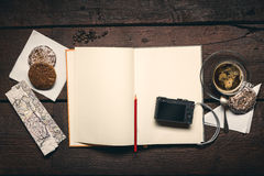 Notepad on the desktop. Compact camera on blank page of notepad on the wooden table, honey-cakes, red pencil and cup of espresso Royalty Free Stock Photo