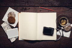 Notepad on the desktop. Compact camera on blank page of notepad on the wooden table, honey-cakes, red pencil and cup of espresso, blank photograph Royalty Free Stock Photos