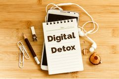 Notepad with Digital Detox text and  pencil , smart phone on woo Stock Photos