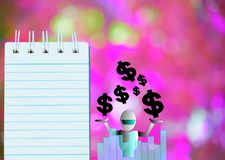 Notepad with dollar and robot  on wood board background.using wallpaper or for education, business photo.Take note of the p Stock Photography