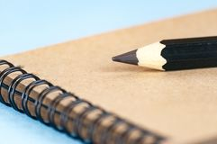 Notepad for drawing from recycled paper. On a spiral mount. A large pencil for sketching. Selective focus royalty free stock image