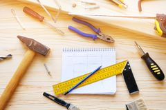 Notepad with drawings and construction tools for building a house or apartment repair, on a wooden table. The workplace of the royalty free stock image