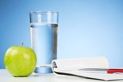 Notepad with a Drink and an Apple Stock Images