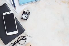 Notepad dzienniczek, wizytówka, szkła, zegar na zaświeca stół Odgórny widok z kopii przestrzenią, mieszkanie Lay zdjęcia stock