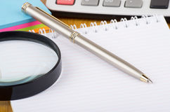 Notepad, electronic calculator, pen and magnifying glass Stock Image