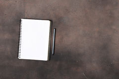 Notepad with empty pages on dark surface with lead pencil. Notepad with empty pages on a dark surface with lead pencil, top view Stock Photos