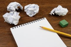 Notepad with empty sheet on a wooden table and crumpled sheets around stock image