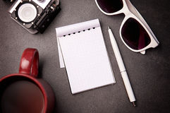 Notepad, exponeringsglas, penna och kopp på tabellen Royaltyfria Foton
