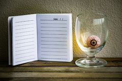 Notepad with eye ball in glass on wood and wall background. Using wallpaper or background for halloween day image. Stock Images