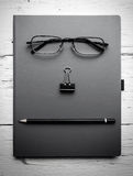 Notepad, eyeglasses, paperclip and pencil on wooden table. Royalty Free Stock Photos