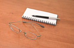 Notepad with eyeglasses and pen Royalty Free Stock Photo