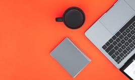 Notepad, filiżanka kawy i laptop, odizolowywamy na czerwonym tle i miejscu dla teksta obraz royalty free