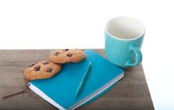 Notepad, filiżanka, pióro w turkusowym kolorze z czekoladowego układu scalonego ciastkami Drewniany stołu i bielu tło Wielki rane Zdjęcie Royalty Free