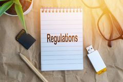 Words REGULATIONS on wooden paper background. Business and education concept royalty free stock images