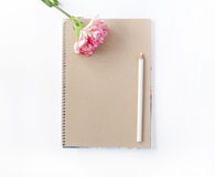 Notepad and flower with white pencil on white Stock Photos