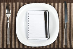 Notepad on food plate Royalty Free Stock Photos