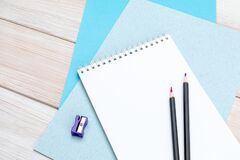 Free Notepad For Notes, A Pair Of Pencils, A Purple Pencil Sharpener And Sheets Of Blue Cardboard On A White Wooden Table Stock Photos - 169806043