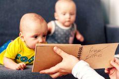 Notebook in the foreground. In the background are twins, a boy and a girl of 7 months. Maternity. Selective focus. Notepad in the foreground. In the background royalty free stock image