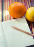 Notepad_with_fruits. Notepad, pensil and fruits. For diet program or recipes royalty free stock images