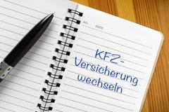 "Note in german language: KFZ -Versicherung wechseln. Notepad with german phrase ""KFZ-Versicherung wechseln"". Translation: change car insurance stock photography"