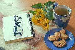 Notepad with glasses and cup of tea with cookies Royalty Free Stock Photo