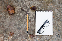Notepad, glasses and pencil on the  floor Stock Photo