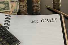 Notepad with 2019 goals text, calculator, pencil, money background. royalty free stock photo