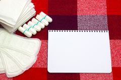 Notepad for gynecological menstruation cyclenotes and woman hygiene protection, menstruation sanitary pad and cotton tampons on th Stock Images