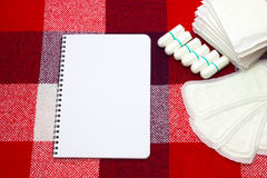 Notepad for gynecological notes and woman hygiene protection, menstruation sanitary pads and cotton tampons on the plaid at home. Notepad and woman hygiene stock images