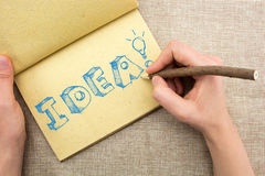 Notepad with hand drawing sketchy Idea word. With light bulb Royalty Free Stock Photography
