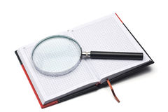 Notepad and hand magnifier. Notepad in the red-black cover and hand magnifier Stock Photography