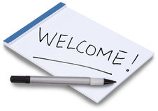Notepad with handwritten Welcome. Notepad isolated with handwritten Welcome! on a white sheet of paper with blue binding and a pen lying on the paper Royalty Free Stock Image