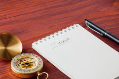 Notepad with handwritten word Trends, pen and compass nearby on wooden board shallow depth of field Royalty Free Stock Photos