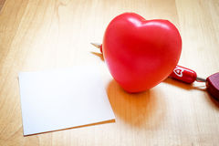Notepad with heart toy and red pen on wooden table,love concept Royalty Free Stock Image
