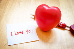 Notepad with heart toy and red pen on wooden table,love concept Stock Images