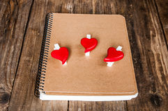 Notepad and hearts on grunge wooden background Royalty Free Stock Photos