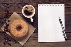 Notepad i kawa z pączkiem obrazy royalty free