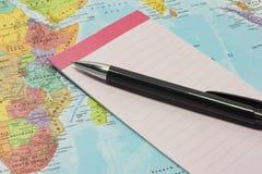 Notepad i pióro na górze mapy Zdjęcia Stock