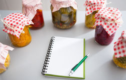 Notepad among jars of pickled vegetables Royalty Free Stock Images